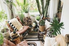 a lush boho sunroom with leather chairs, lots of potted greenery and some wicker and woven touches