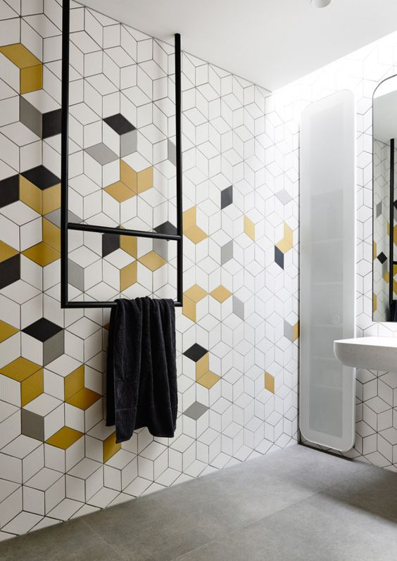 a minimalist bathroom with white, grey, mustard and geo tiles, a narrow window, black fixtures and white appliances