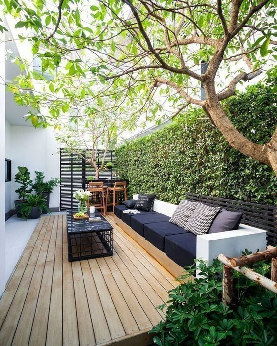 a modern monochromatic terrace with a wooden deck, a large built-in sofa, a small bar space and a whole living wall