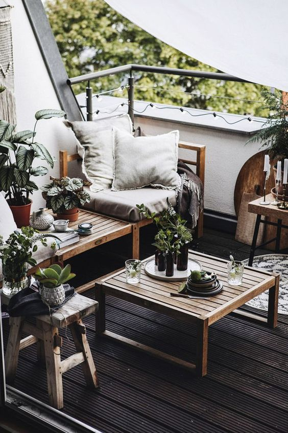 a monochromatic balcony with a black floor, natural wooden furniture, neutral textiles, potted greenery and candles