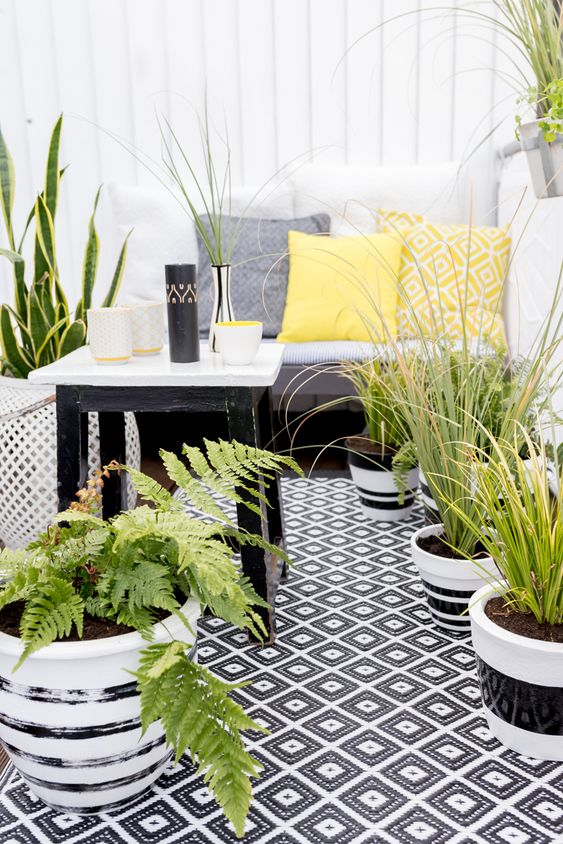 a monochromatic balcony with printed textiles, potted greenery and succulents and simple and stylish furniture