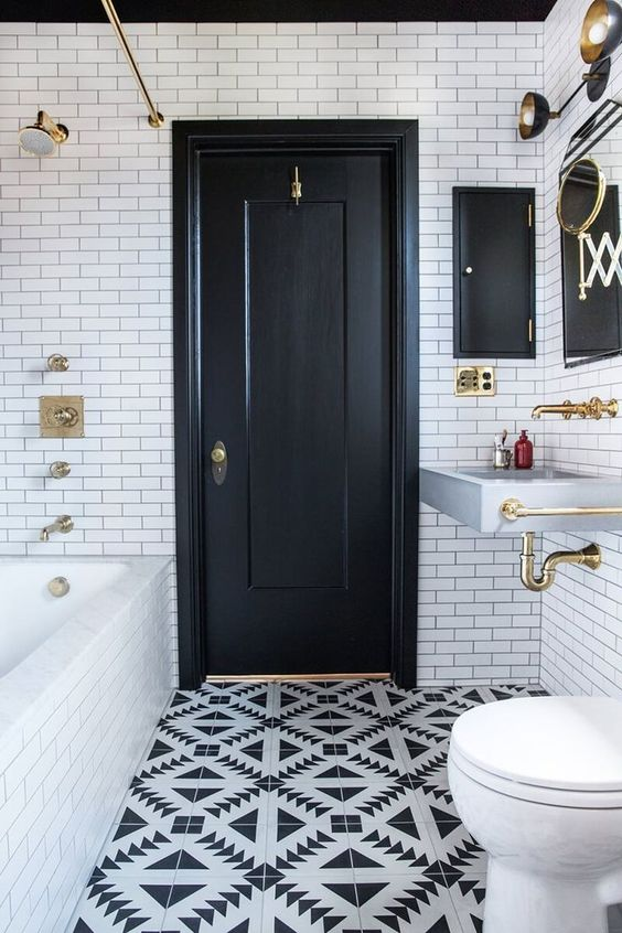 a monochromatic bathroom with white subway tiles, black and white geo ones, a wall-mounted sink and gold fixtures
