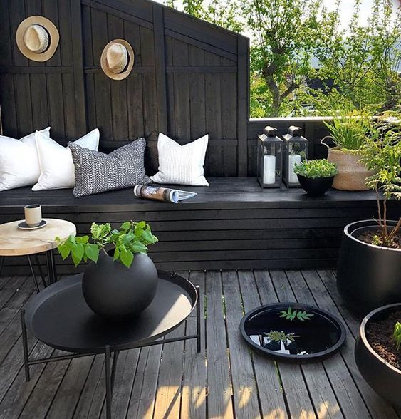 a moody terrace with black wood, light pillows, potted greenery and candle lanterns looks fresh and stylish