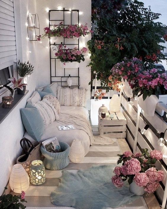a neutral and pastel balcony with boho textiles, candle lanterns, potted greenery and lights