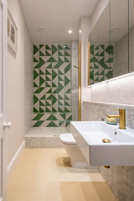 a neutral bathroom with small scale tiles, a green and white tile wall in the shower space, white applainces and brass touches