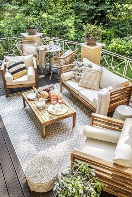 a neutral summer terrace with wooden furniture, potted plants, rattan chairs and lots of cool textiles