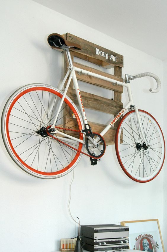a pallet shelf holding a bike is a cool idea for a rustic or industrial space and it can be placed anywhere