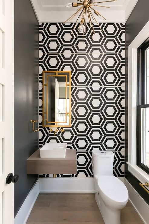 a refined and chic bathroom with black and white geo tiles, a wall-mounted vanity and white appliances and gold touches