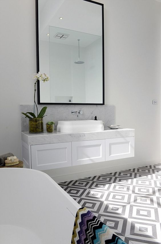 a refined bathroom with a grey and white geo tile floor, a floating vanity and white appliances plus an oversized mirror