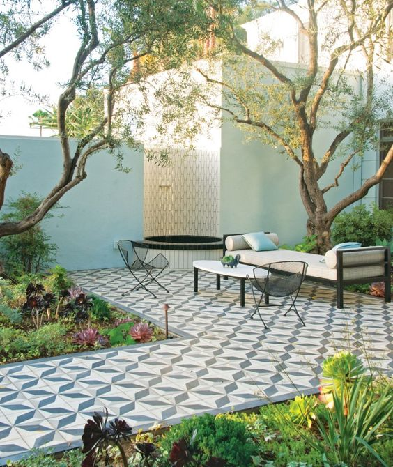 a refined modern terrace with a Mediterranean feel with greenery and succulents, a tiled deck, metal furniture and a fountain