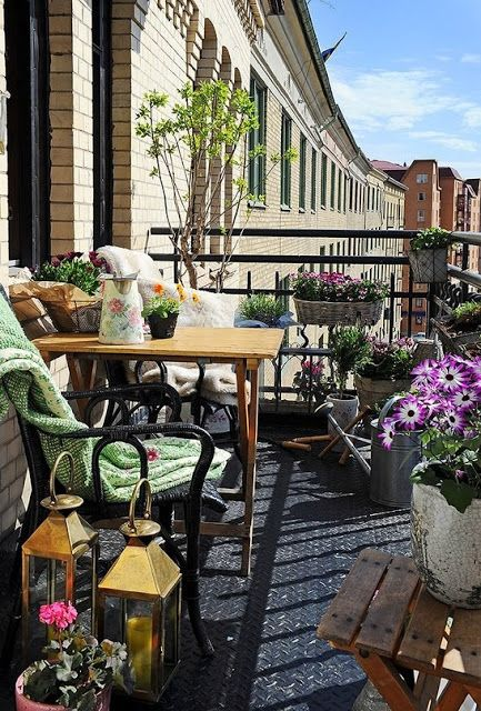 a refreshing summer balcony with potted greenery and blooms, rattan and wooden furniture, candle lanterns and textiles