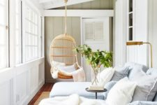 a relaxing small sunroom with striped blue lounge chairs, a lamp, a table and a hanging wicker chair