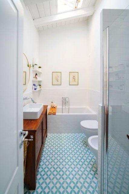 a serene bathroom with a skylight, done in white and with a blue geo tile floor plus a stained wooden vanity