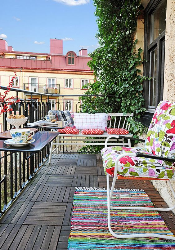 a simple and colorful balcony with bright textiles, some metal furniture and railing tables plus greenery