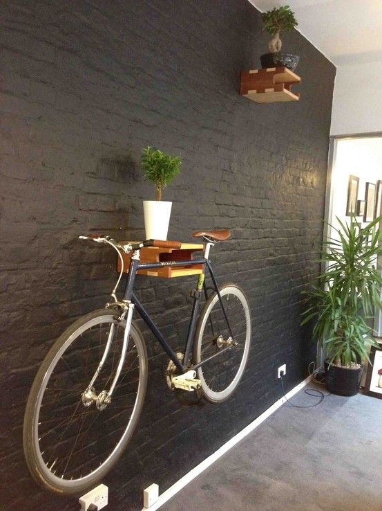 a simple and colorful shelf for holding a bike, with potted greenery is a cool idea to store your bike anywhere you want