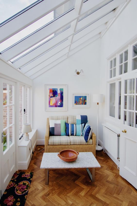 a simple and modern sunroom with a small wicker sofa with colorful pillows, artworks and a coffee table