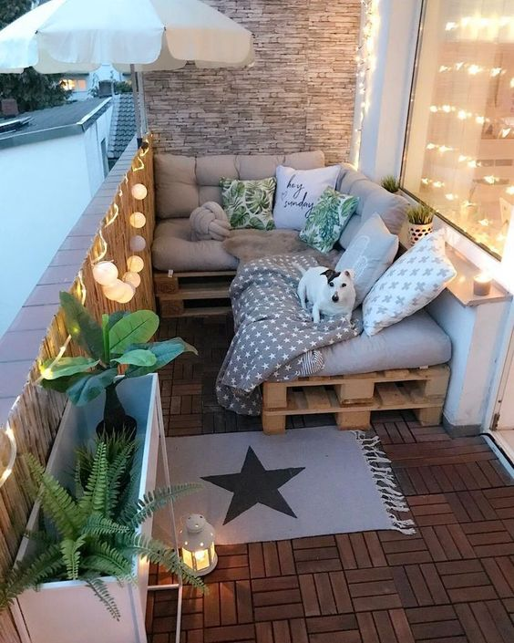 a small and cozy balcony with a pallet L-shaped sofa, printed pillows, plants in pots, lights and candle lanterns