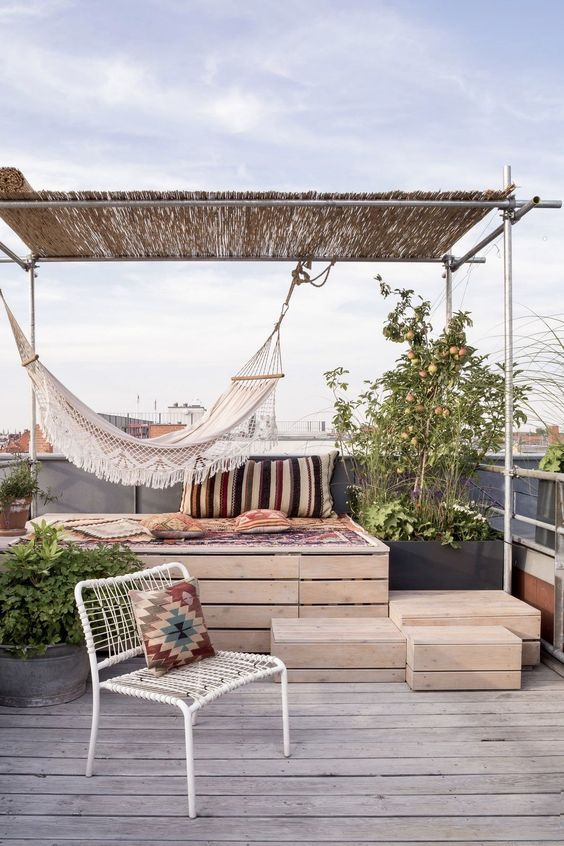 a small and simple terrace with a storage daybed, a metal chair, boho textiles, a hammock and some greenery in pots