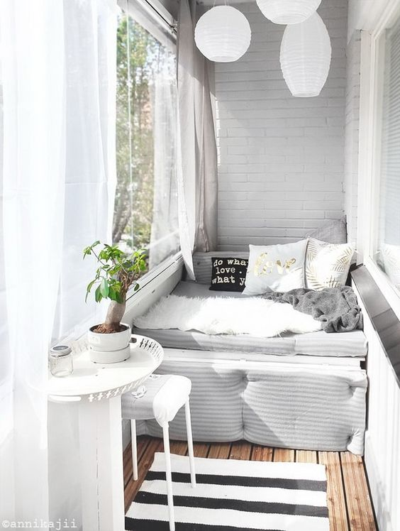 a small balcony with a daybed, a tiny table and stool, paper lanterns and sheer curtains is very welcoming