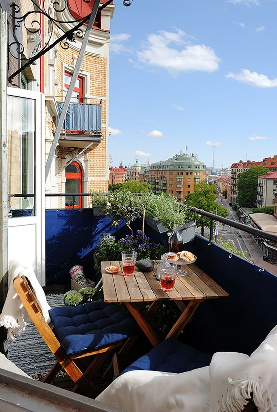 a small balcony with navy railing and upholstery, potted greenery and blooms and folding wooden furniture