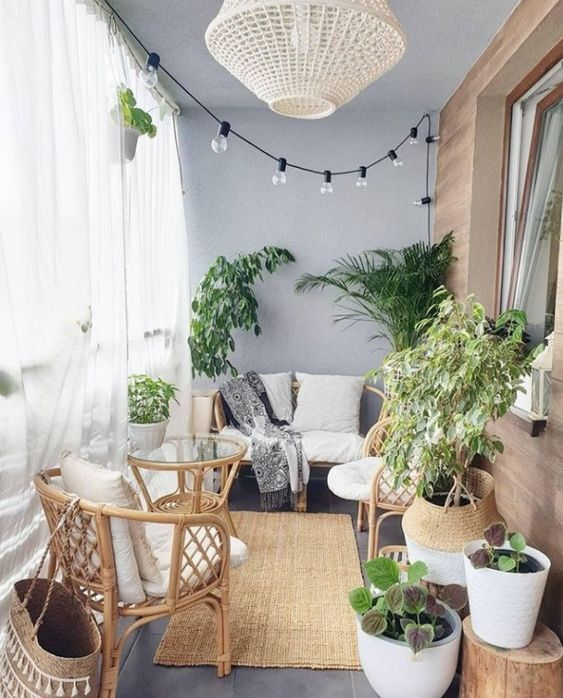 a small balcony with sheer curtains, lights, a wicker lamp, rattan furniture, statement plants and baskets is very cozy