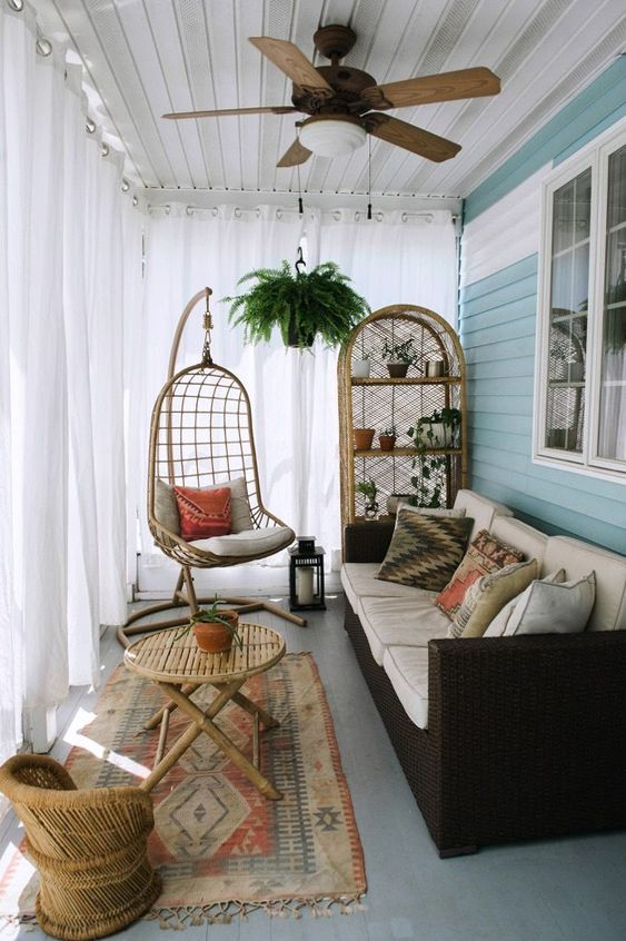 a small boho sunroom with a dark sofa, wicker furniture and a hanging chair plus potted greenery