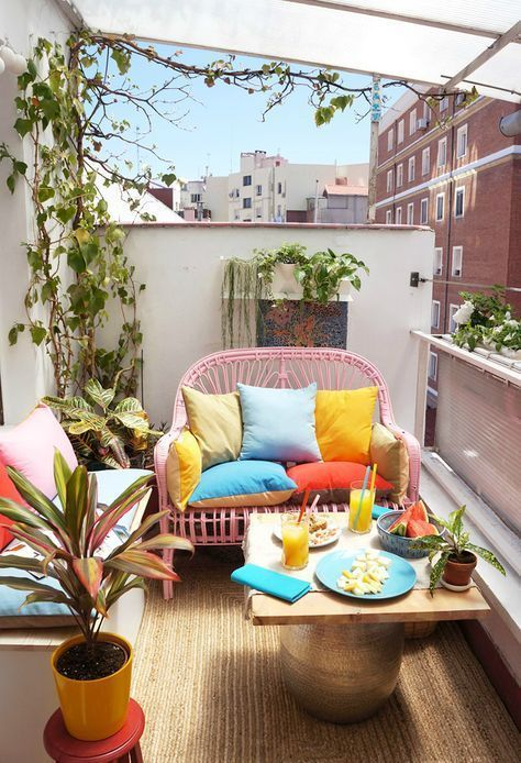 a small bright balcony with a pink loveseat, a small table, a white bench with storage, potted greenery and bright pillows