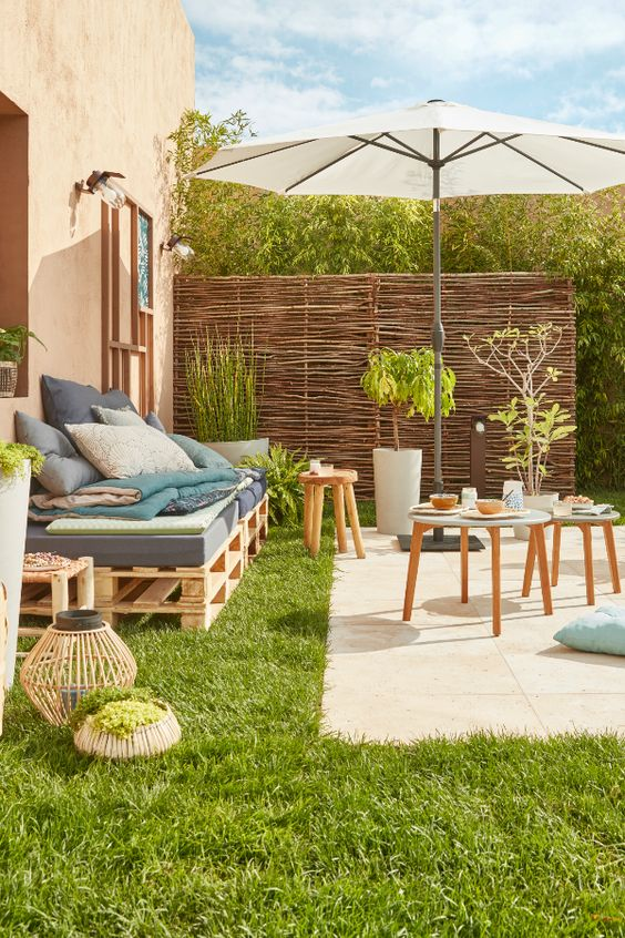 a small rustic summer terrace with a tiled space, a pallet sofa, wooden stools and potted greenery and candle lanterns