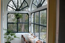 a small sunroom turned into a meal space, with a windowsill table and potted greenery