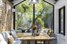 a small sunroom with a dining space, wall and pendant lamps, with a large L-shaped bench and a dining table