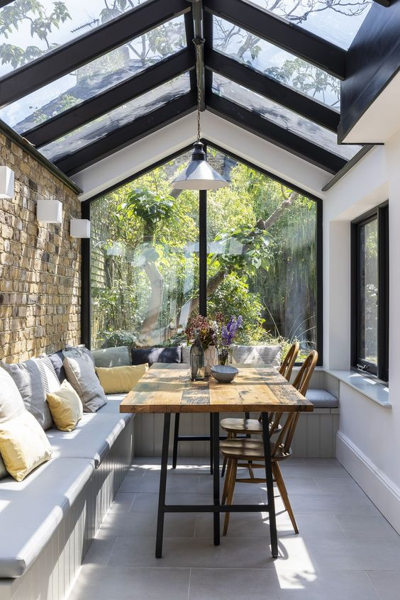 a small sunroom with a dining space, wall and pendant lamps, with a large L shaped bench and a dining table