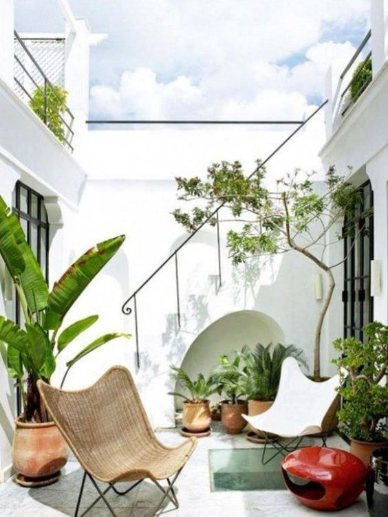 a small terrace with a couple of chairs, potted plants, and a bold red candle lantern is chic and stylish