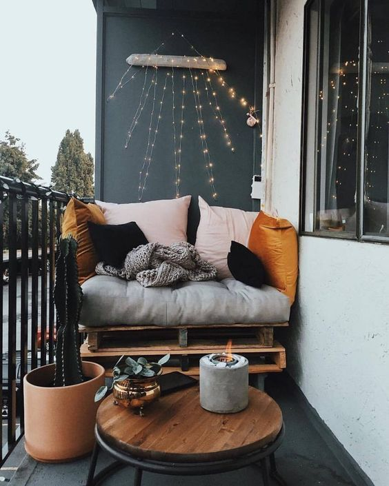 a small yet chic balcony with a pallet seat, colorful pillows, a table, a cactus and a candle in a concrete candleholder