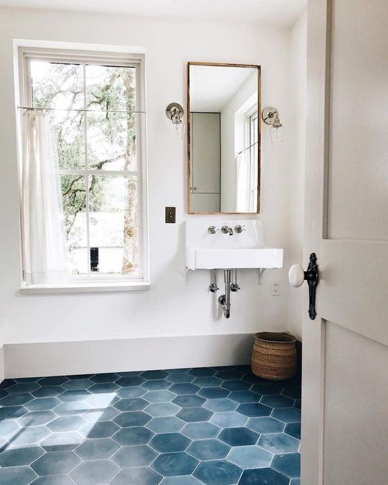 a stylish bathroom in neutrals, with a blue hex tile floor and white appliances plus a basket for storage and a long mirror