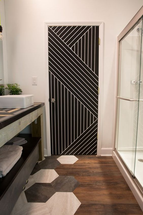 a stylish bathroom with a floor transition - from stained wood to hexagon tiles and a geometric stenciled door