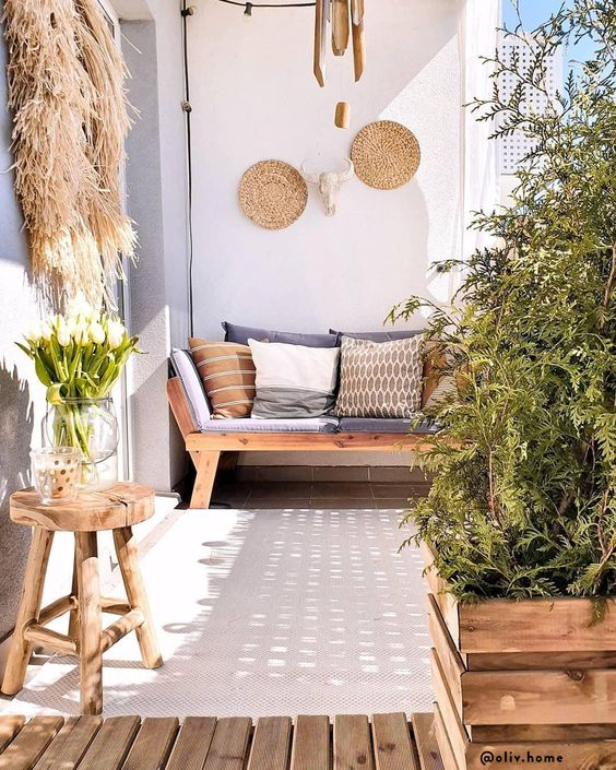 a summer balcony in neutrals, with wooden furniture, crate pots with greenery, decorative baskets, pampas grass and printed pillows