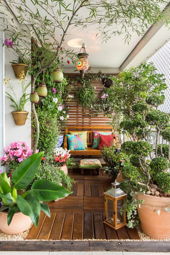 a summer balcony turned into a garden, with potted blooms and greenery, candle lanterns and some wooden furniture