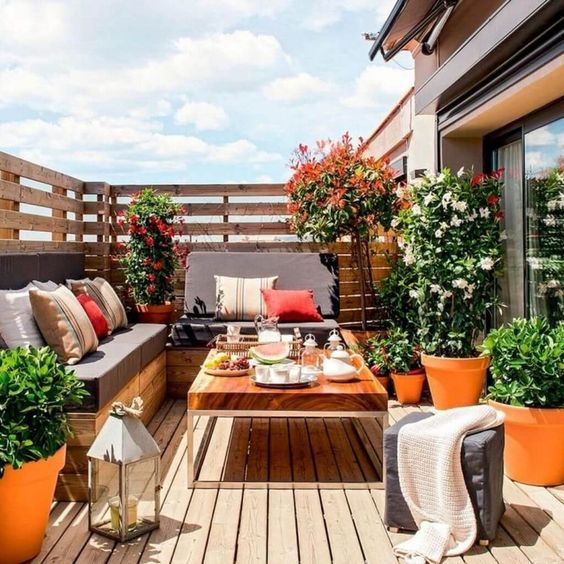a summer balcony with a wooden deck and furniture, potted blooms and greenery and bright pillows plus candle lanterns