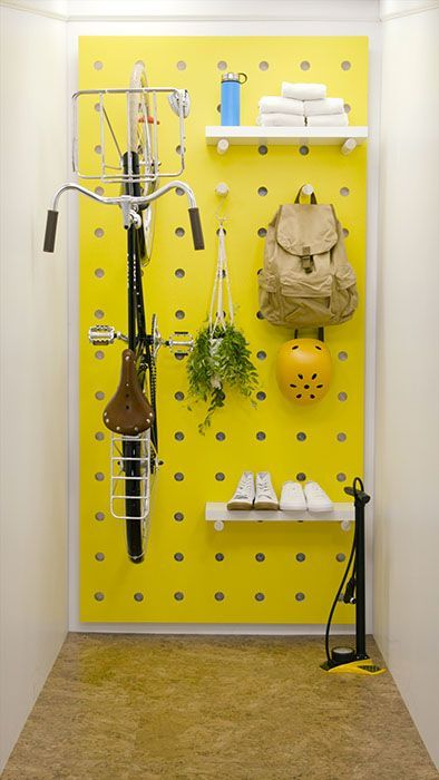 a sunny yellow pegboard with shelves, hooks and a bike holder is a lovely idea to store a lot of things and without sacrificing any floor space