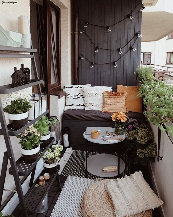 a tiny monochromatic balcony with black and white walls, blakc furniture, potted greenery and blooms and various pillows and rugs
