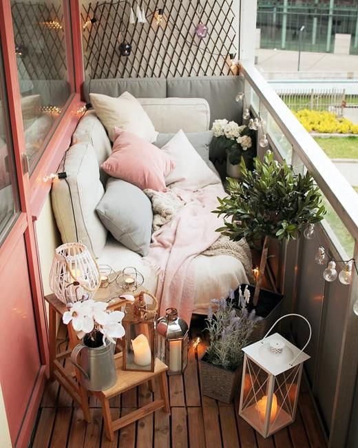 a tiny narrow balcony with pastel textiles and pillows, potted greenery and blooms, candle lanterns and wooden furniture