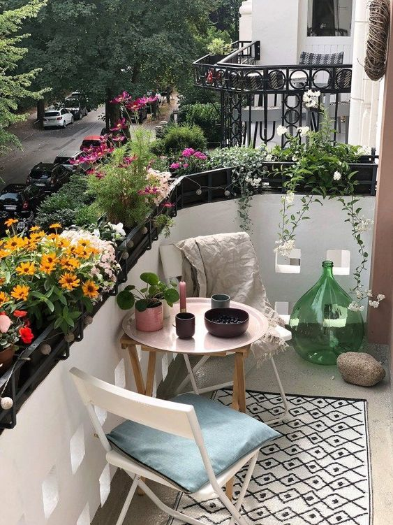 a tiny summer balcony with lots of potted blooms, wooden and metal furniture and pretty accessories