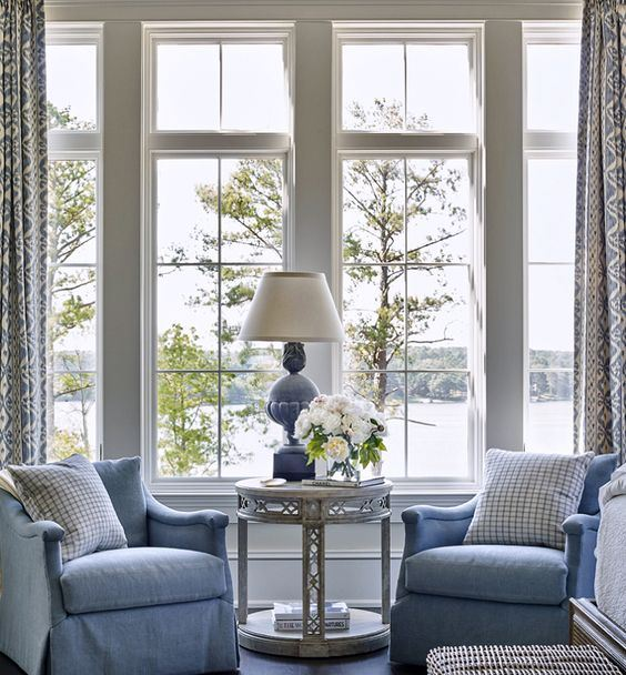a vintage coastal sunroom with blue furniture and a lamp, a woven chest, an elegant table and printed curtains