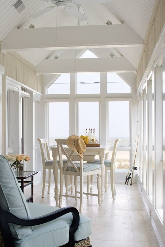 a vintage inspired coastal sunroom with white and black vintage furniture, ligth blue upholstery, chic sea views