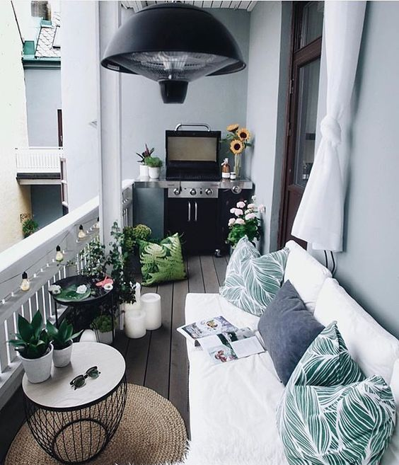 a welcoming balcony with a white L-shaped sofa, printed pillows, a grill, potted greenery and blooms