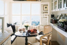 a welcoming small sunroom turned into a dining space, with storage cabinets, an L-shaped bench with storage and chairs