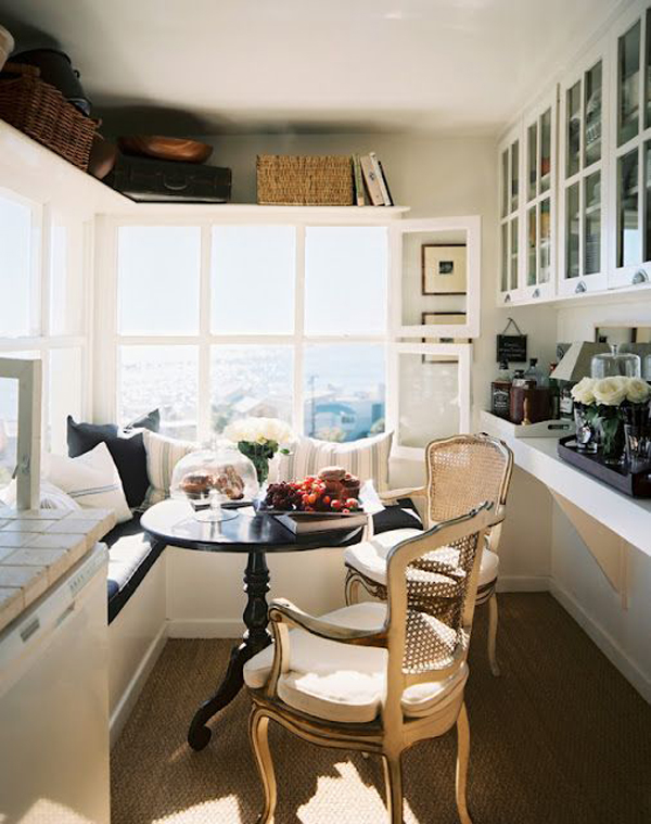 a welcoming small sunroom turned into a dining space, with storage cabinets, an L shaped bench with storage and chairs