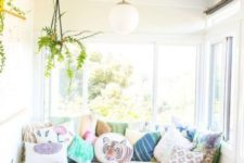 a welcoming sunroom with a sofa and lots of pillows, with footrests and potted greenery