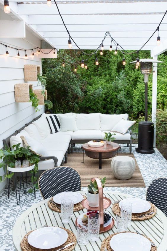 a welcoming terrace with an L-shaped bench, a jute rug, a copper table and some greenery on the wall