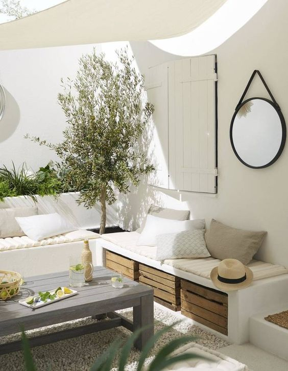 a white Mediterranean terrace with built-in benches, greenery and a tree, crates for storage and a small roof